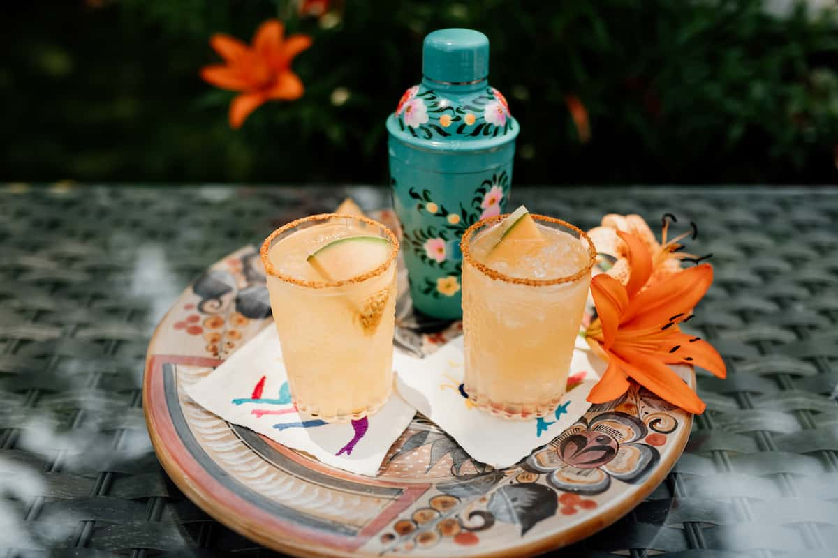two Cantaloupe Melon Margaritas on a Mexican platter and a turquoise hand painted cocktail shaker