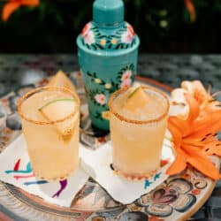 two glasses of melon margarita on a serving tray with a turquoise cocktail shaker and orange lily