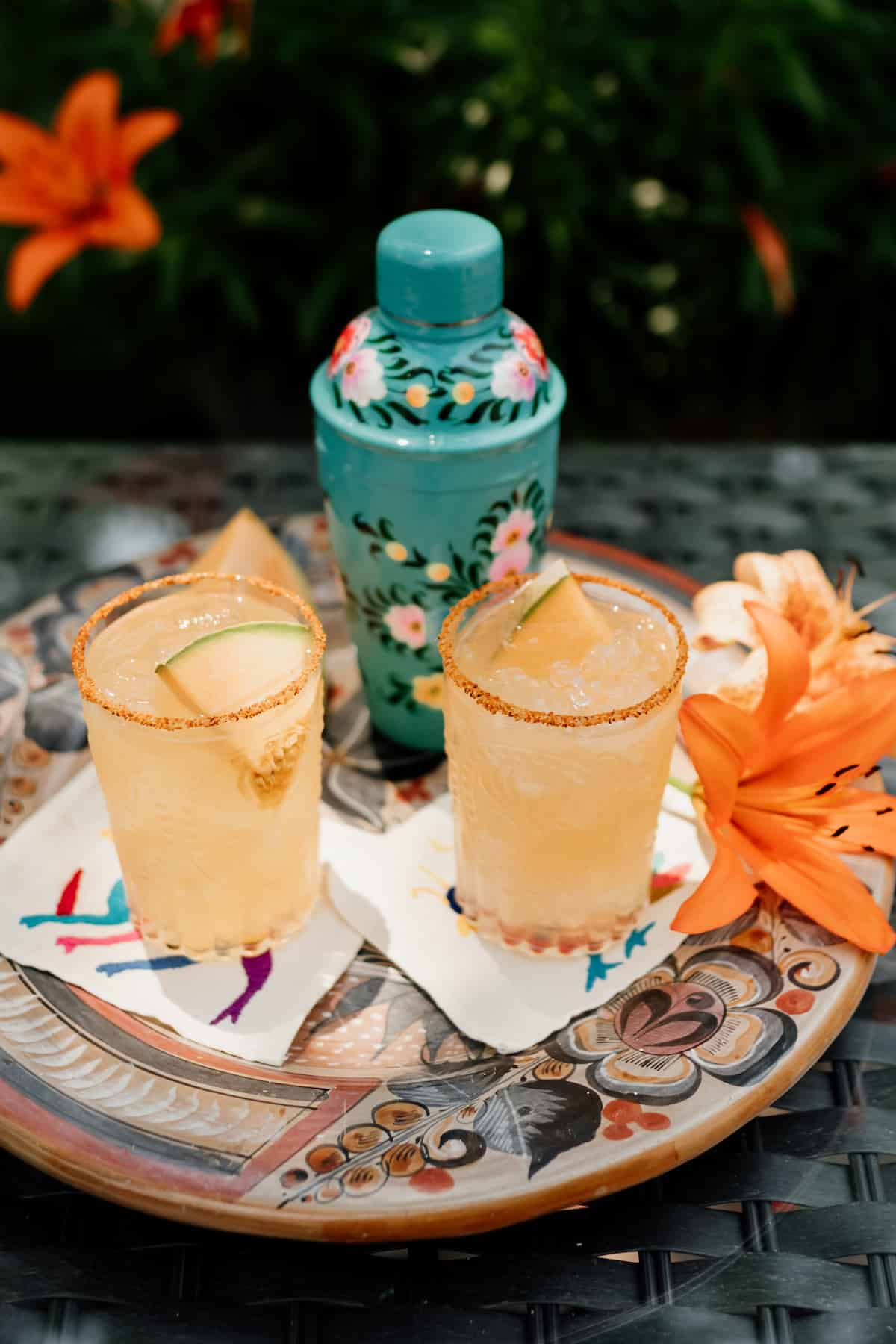 two glasses of Cantaloupe Melon Margaritas rimmed with Tajin and Lilly flowers on the side and cocktail shaker in the background