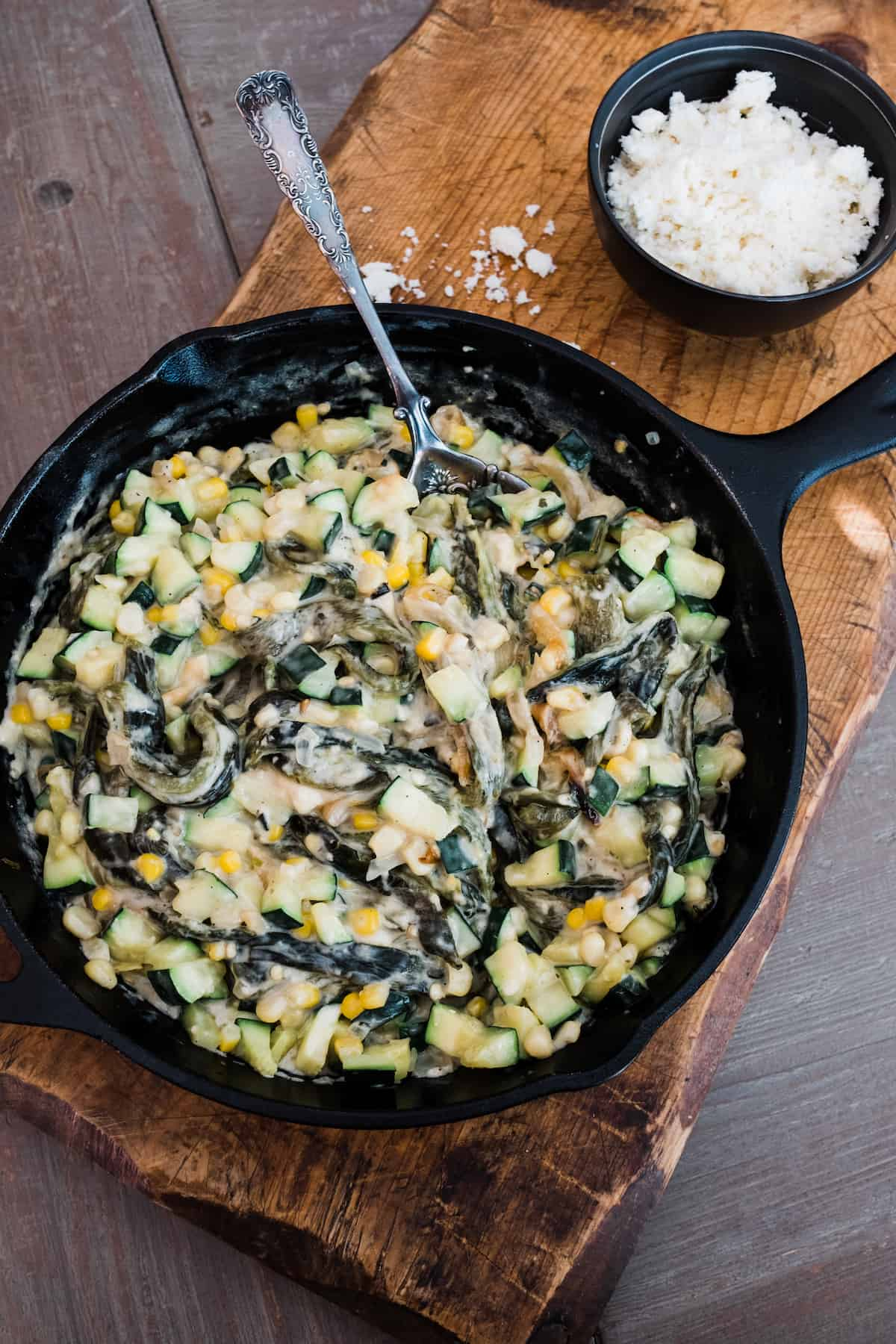 Creamy Zucchini, Corn, and Poblano Rajas in an iron skillet on a wooden board