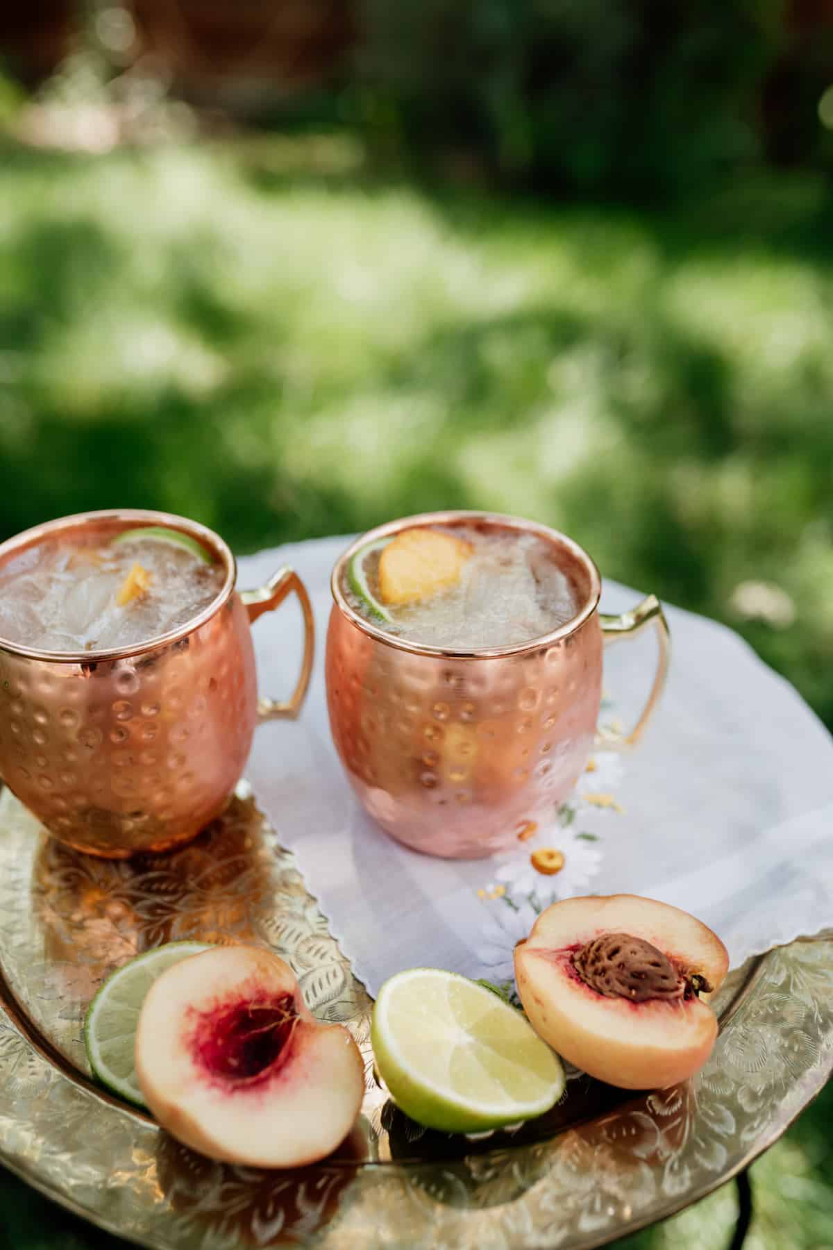two copper mugs filled with peach kentucky mule on a silver platter