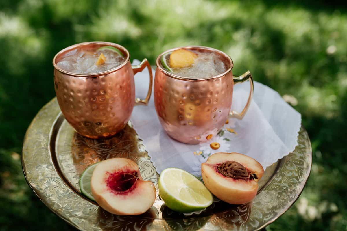 silver serving platter with two peach kentucky mule cocktails with a halved peach and a halved lime