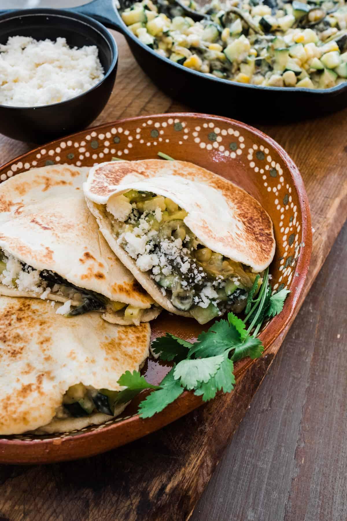 three Gorditas de Harina filled with calabacitas con elote y Rajas de poblano on a Mexican brown plate