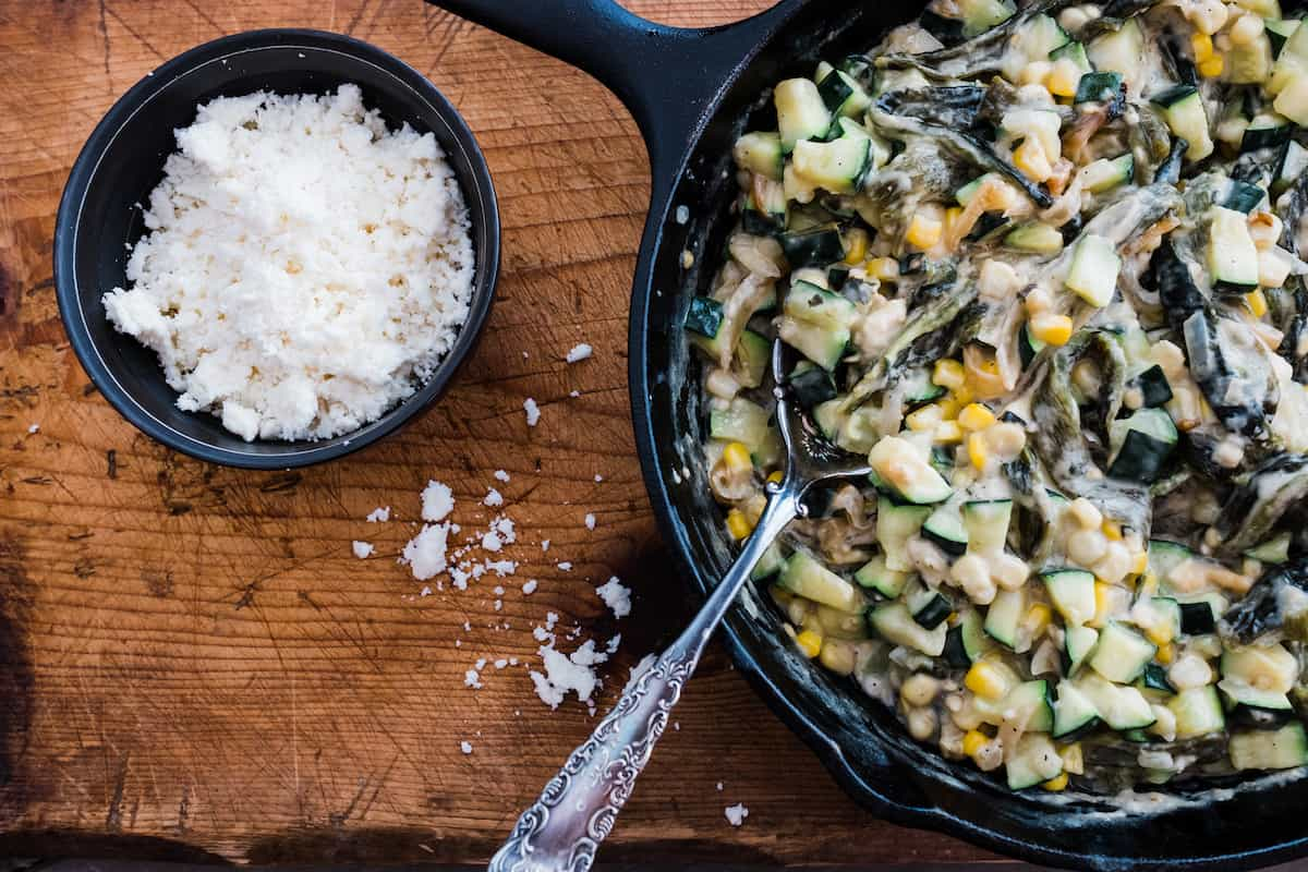 Creamy Zucchini, Corn, and Poblano Rajas garnished with Queso fresco on a wooden board