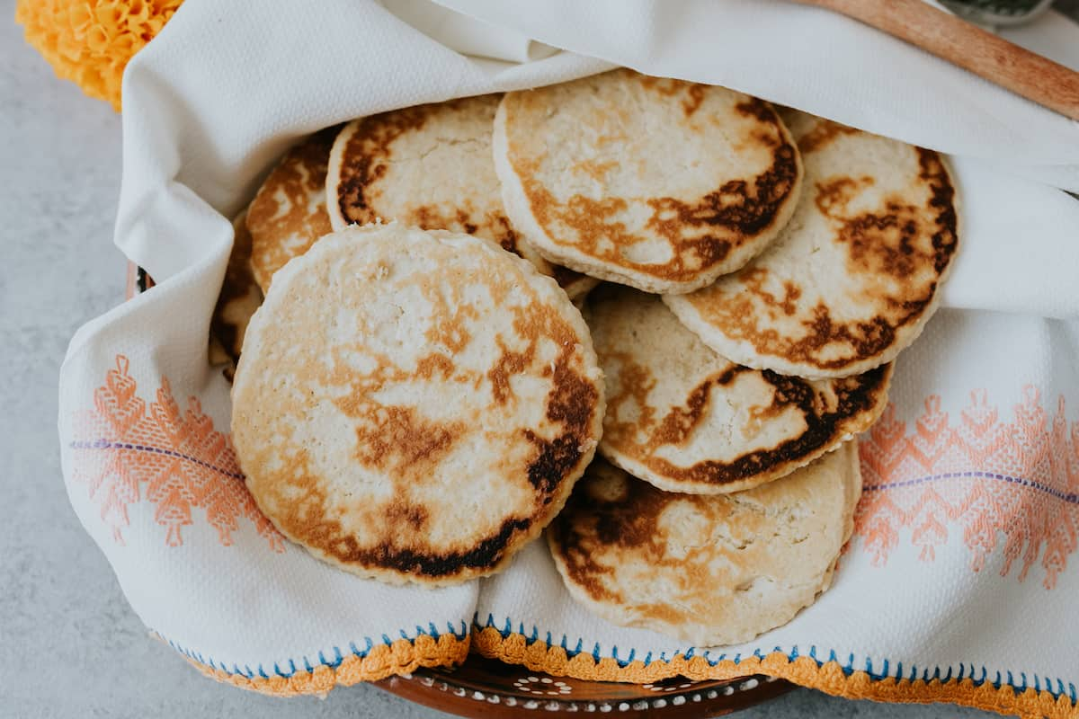 stack of Sweet Gorditas on a Mexican platter in a white linen cloth
