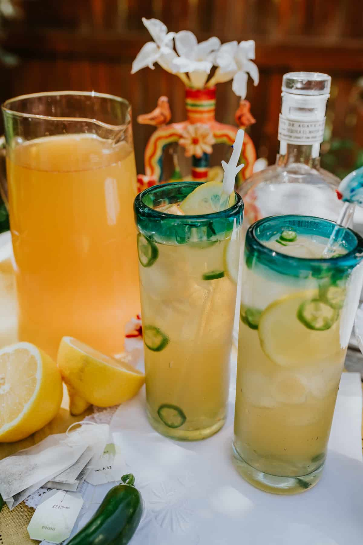 tall glass pitcher of green tea lemonade in the background with two spicy arnold palmer margaritas in green rimmed glasses in the foreground