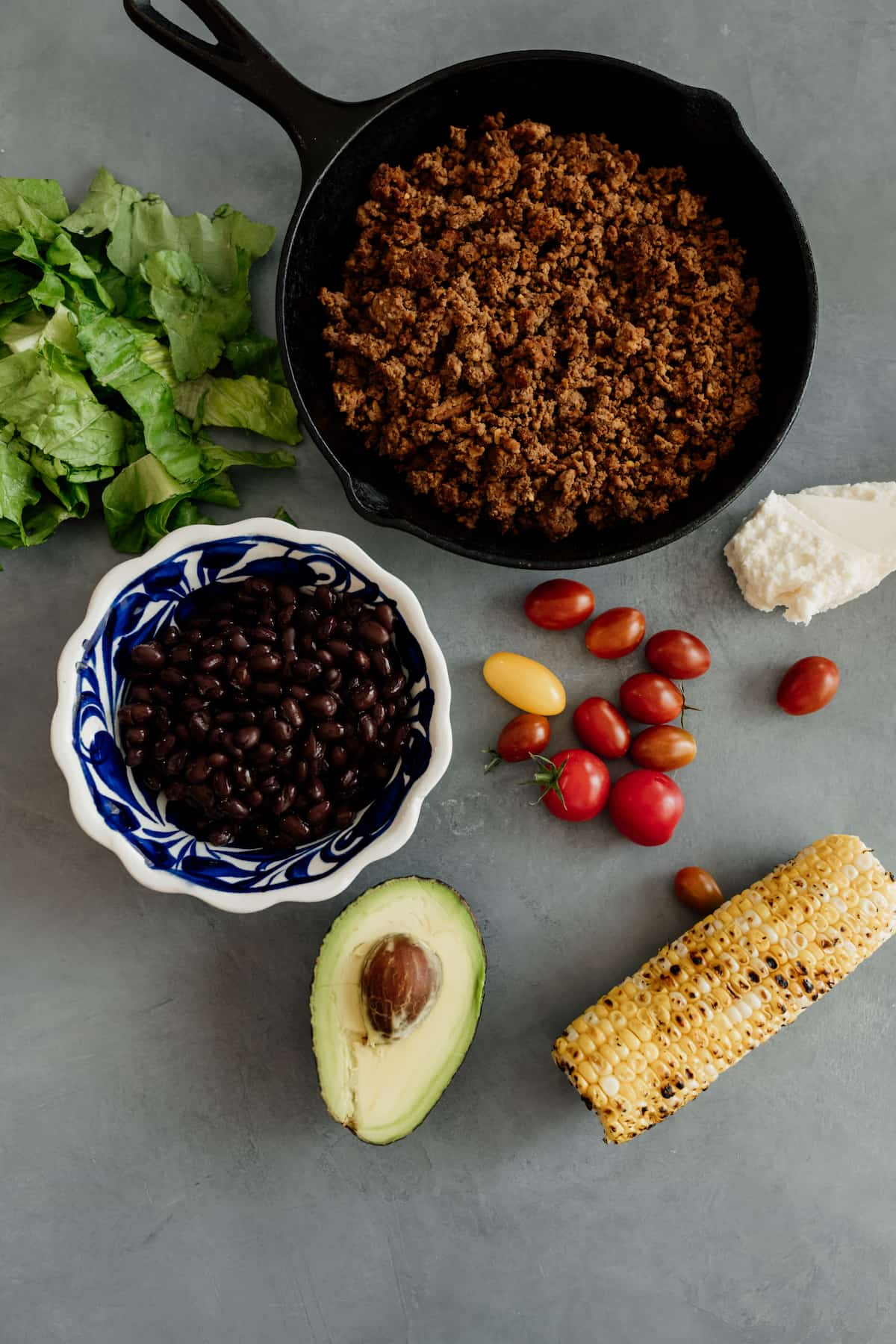 skillet with ground bison and ingredients for a taco salad - corn, avocado, tomatoes, black beans