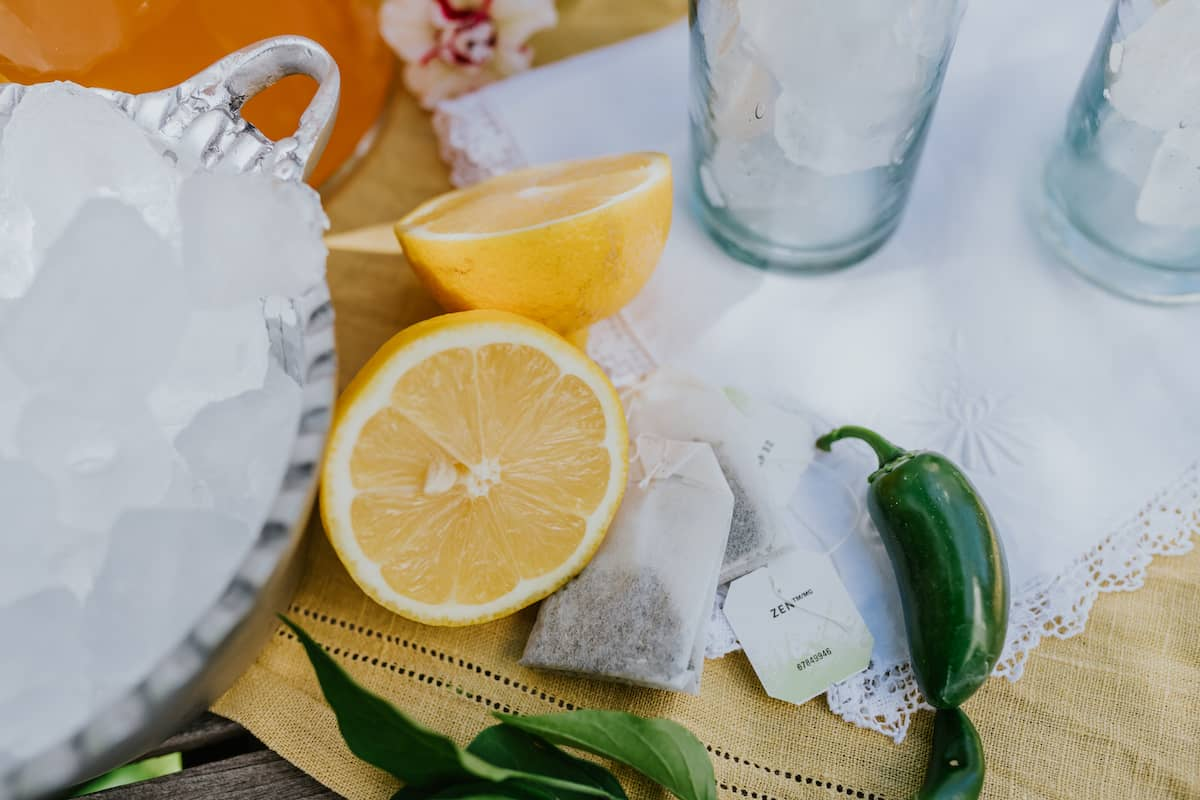 flat lay shot of a halved lemon, green tea bags, fresh jalapeños, a silver bowl of ice and two collins glasses on a white embroidered cocktail napkin