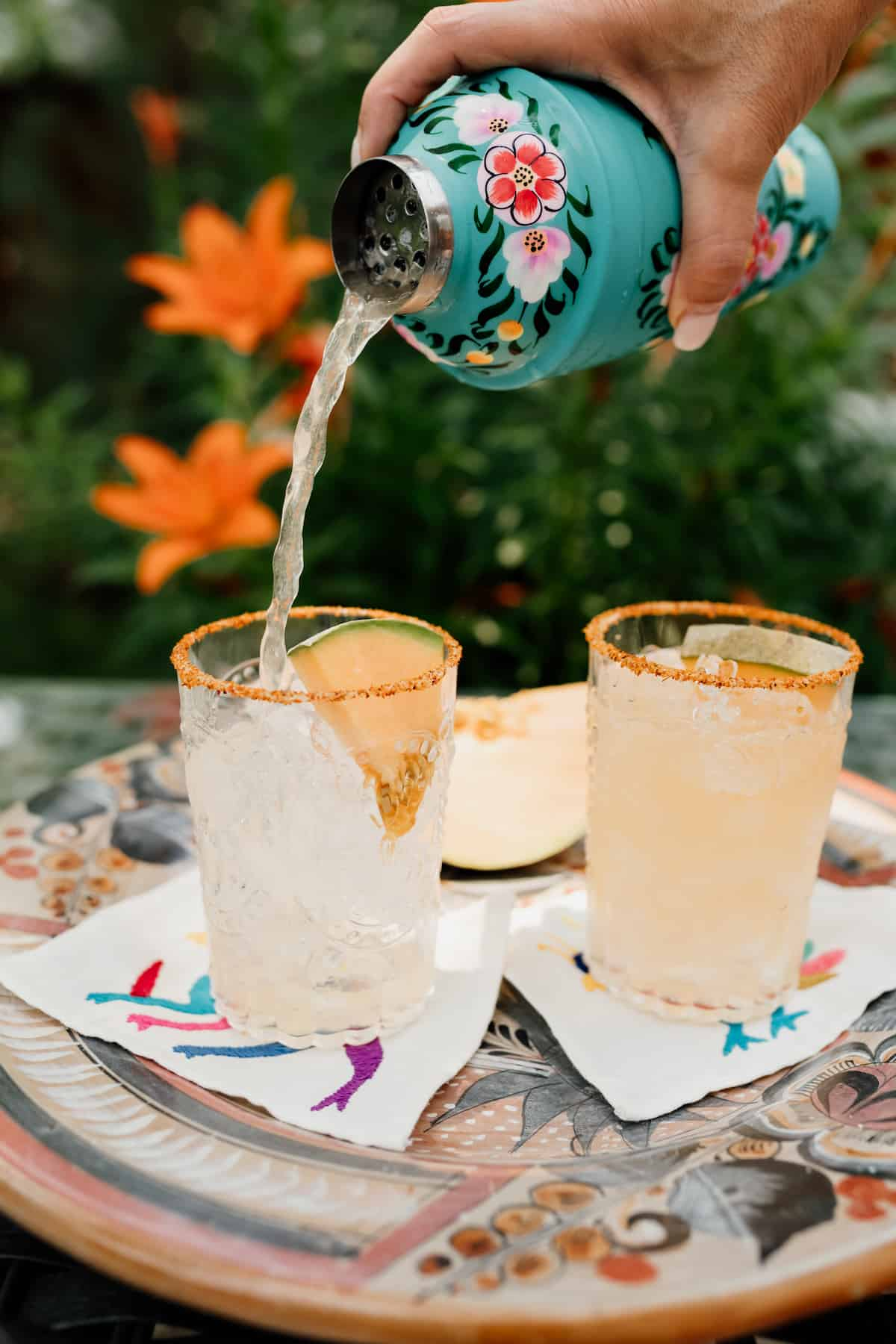 Cantaloupe Melon Margarita being poured into two glasses filled with ice
