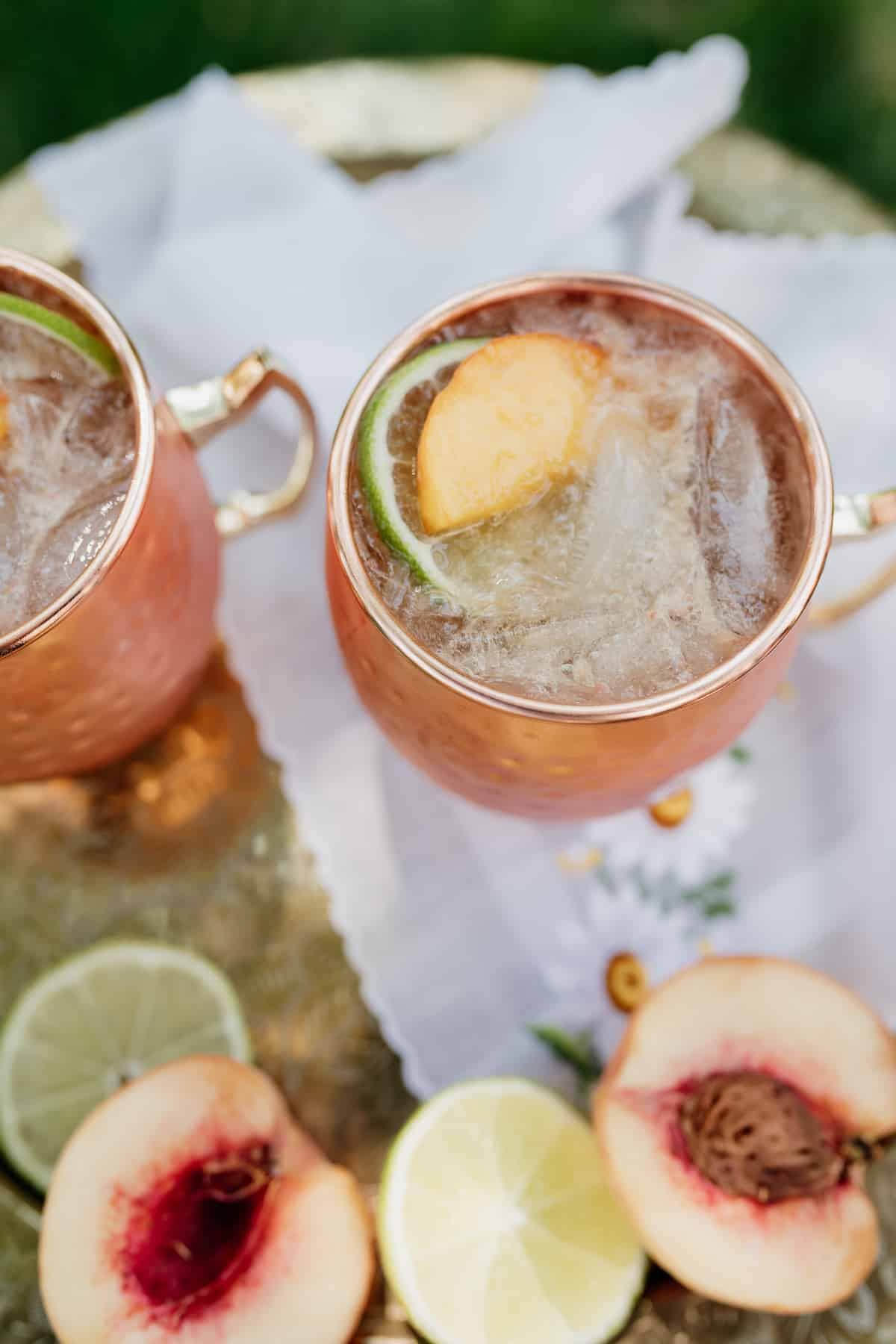 overhead shot of two copper mugs of peach kentucky mules on an embroidered napkin