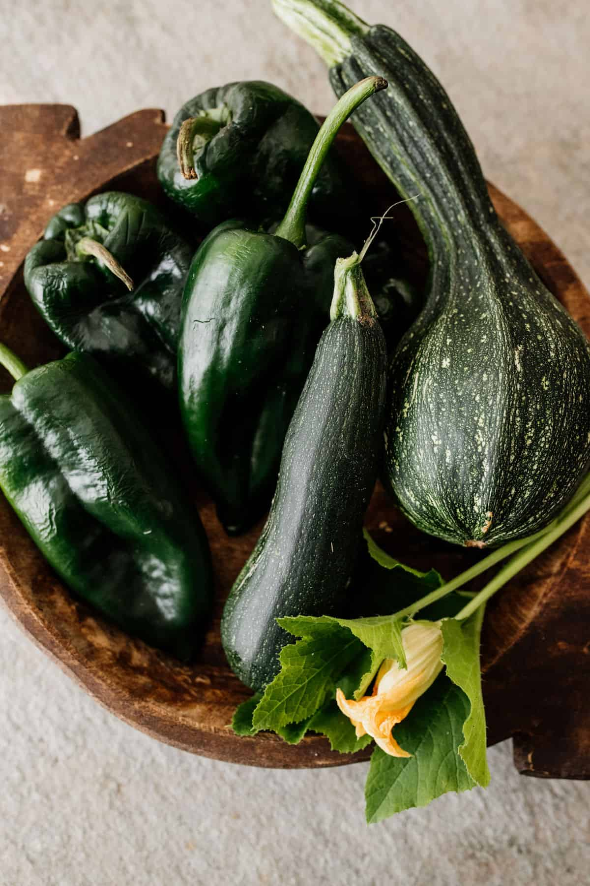 a brown wooden bowl filled with zucchini and poblanos from the garden