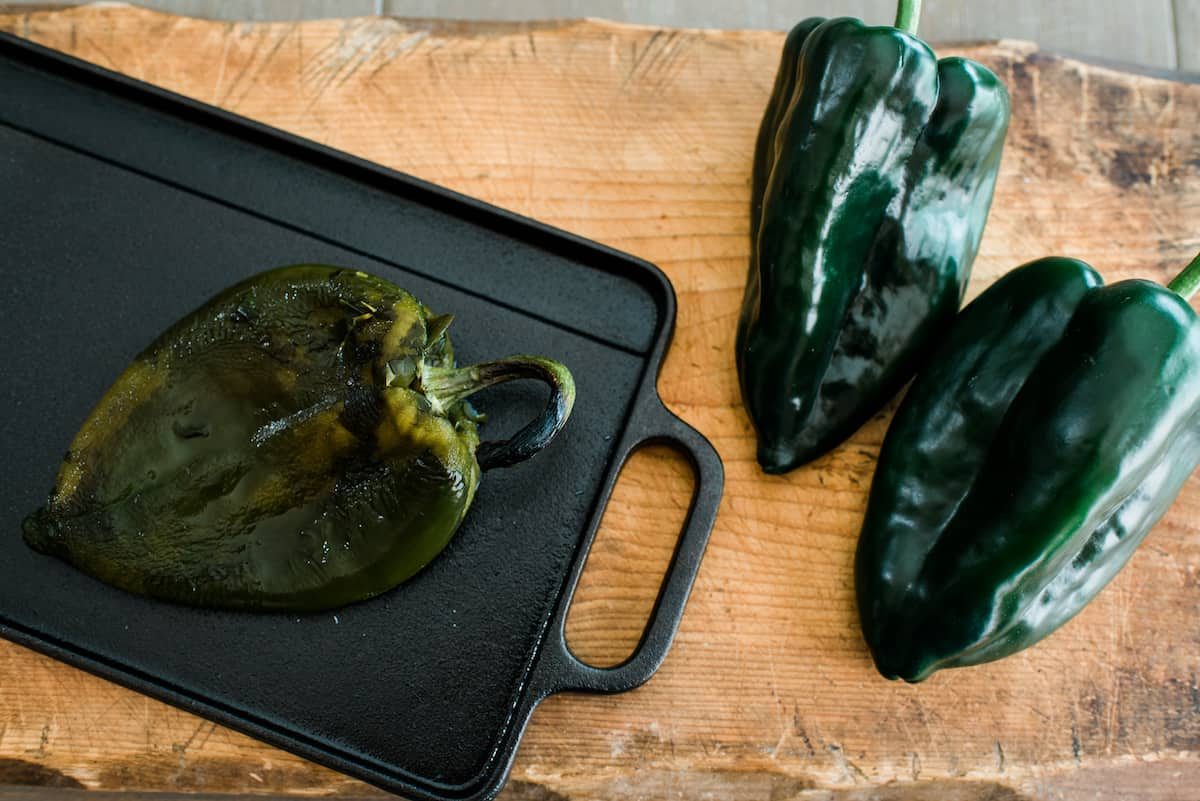 two fresh poblano peppers on a wooden board and one roasted on a cast iron skillet