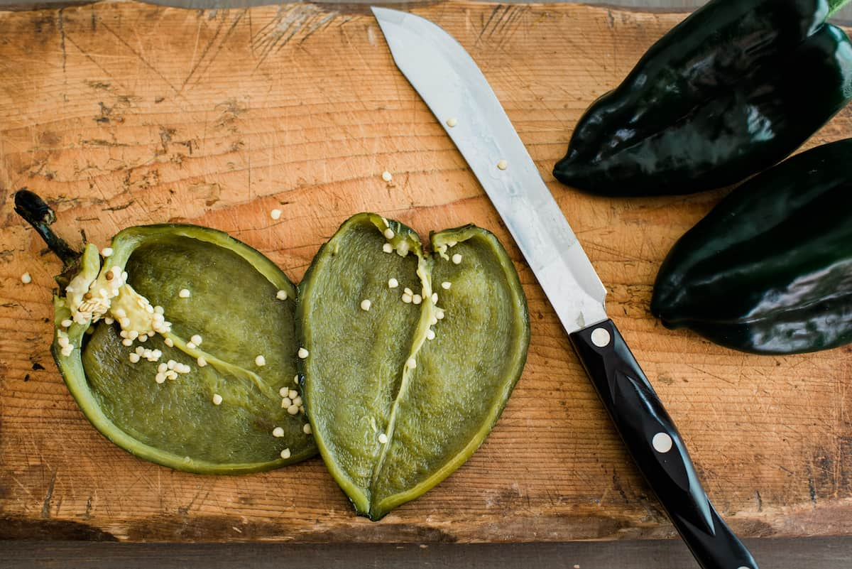 roasted poblano split in half with knife besides it on a wooden cutting board