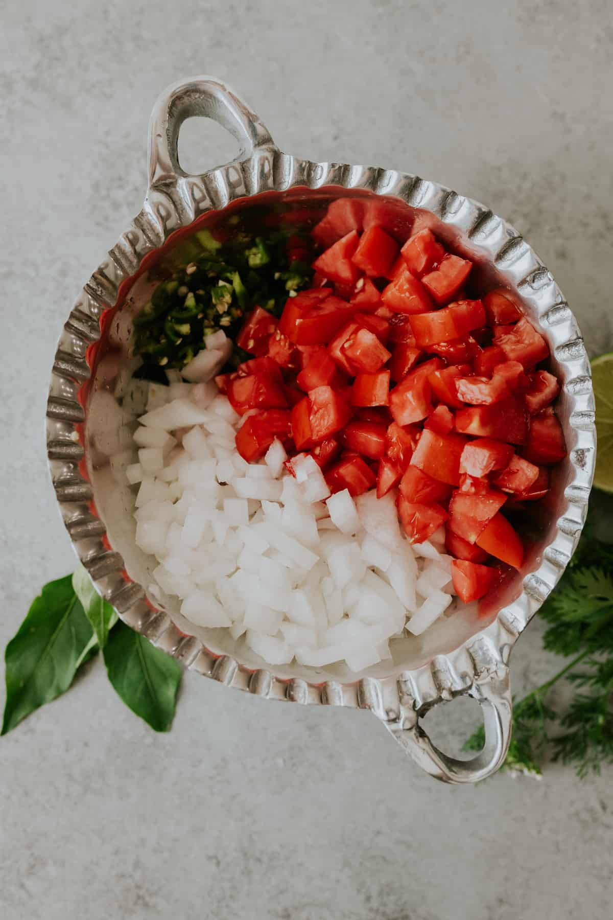 Chopped salsa bandera ingredients arranged in a large silver serving bowl with two handles