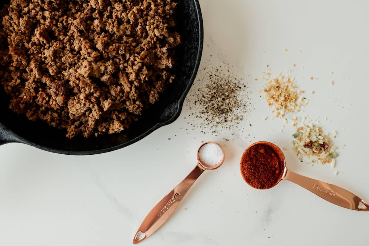 ground beef bison in skillet and spices seasonings on the side