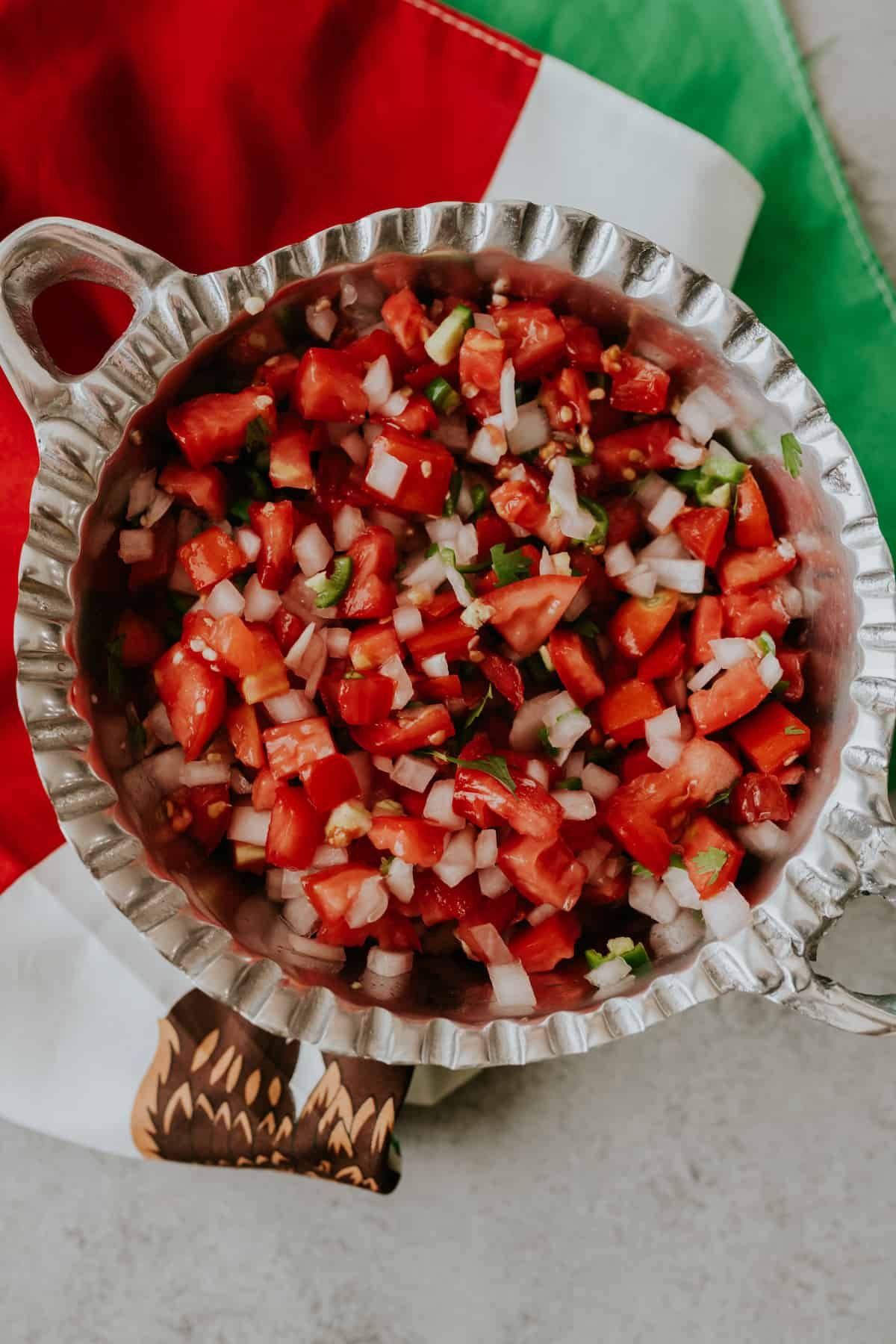 Freshly chopped Pico de Gallo salsa in a silver bowl with a red, white, and green Mexican flag underneath