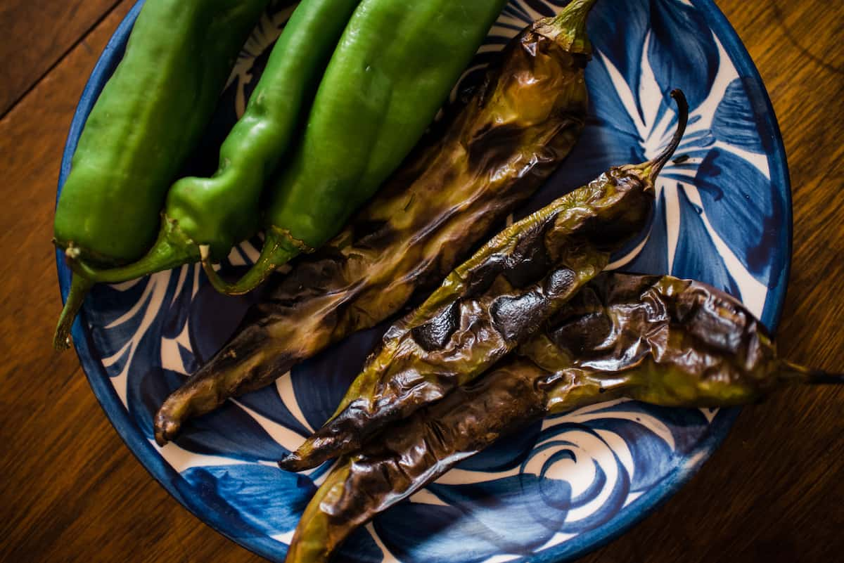 fresh and roasted Chile peppers on a blue and white plate